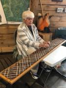 Guild member using a continuous warp method to weave a scarf.